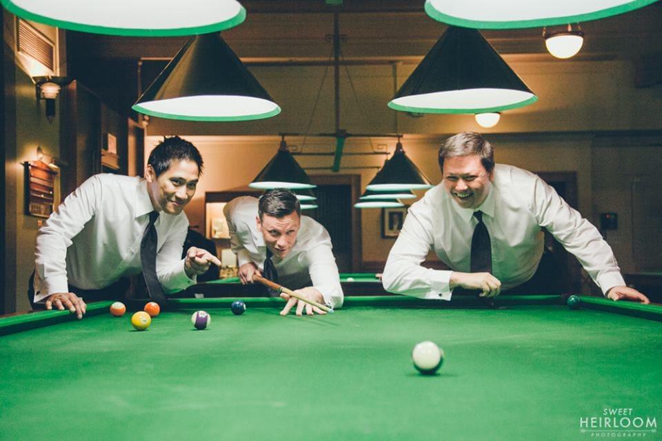 groomsmen playing pool wedding